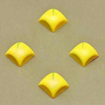 Four square yellow sweets on a light table