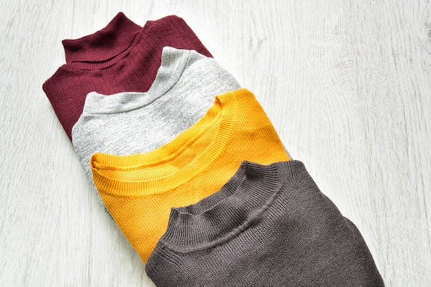 Four sweaters on a wooden background fashion concept