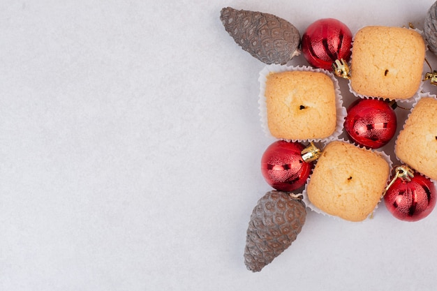Four sweet cupcakes with pinecone and christmas balls