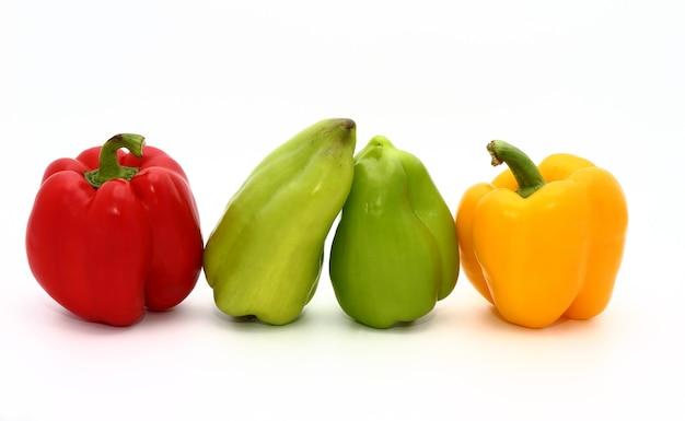 明るい背景に赤、緑、黄色の色の4つの甘い熟したピーマン。天然物。自然な色。閉じる。