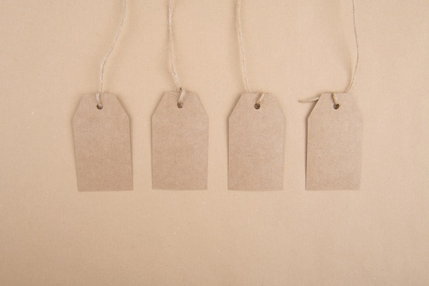 Four tags of recycled kraft paper hanging from a rope on a kraft paper. flat lay