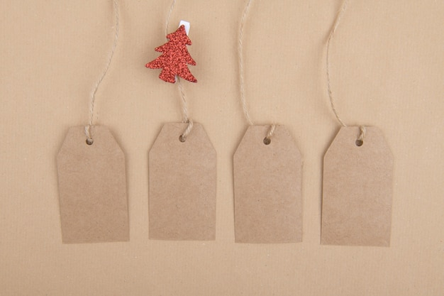 Four tags of recycled kraft paper hanging from a rope with a clothespin with a red christmas tree on kraft paper. flat lay