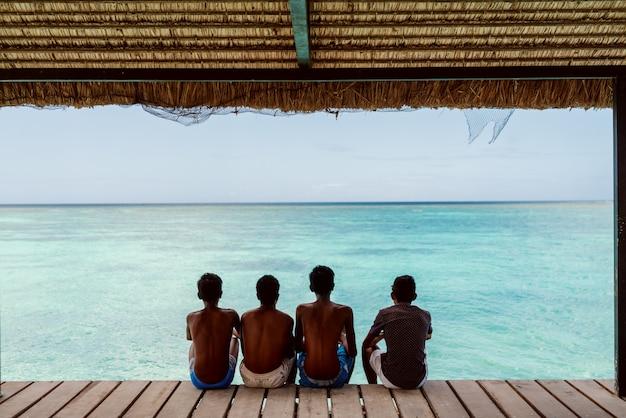 ドックに座って美しい青い海を見ている4人の日焼けした少年。背中を向けた。