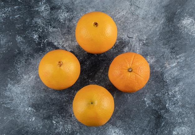 Четыре вкусных апельсина на мраморном столе.