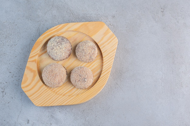 Four tasty truffle balls placed on wooden plate.