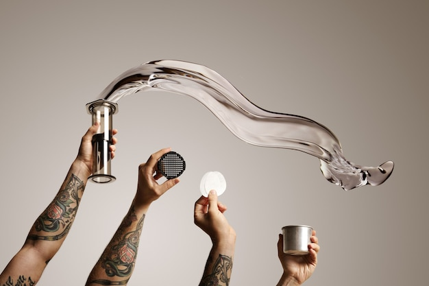 Four tattooed hands holding aeropress and spare parts with water flying out of aeropress on white alternative coffee brewing commercial