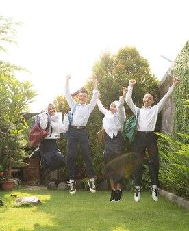 卒業発表で中学生の制服を着て元気に飛び跳ねる4人のティーンエイジャー