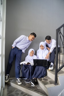 中学生の制服を着た4人のティーンエイジャーがノートパソコンを共有