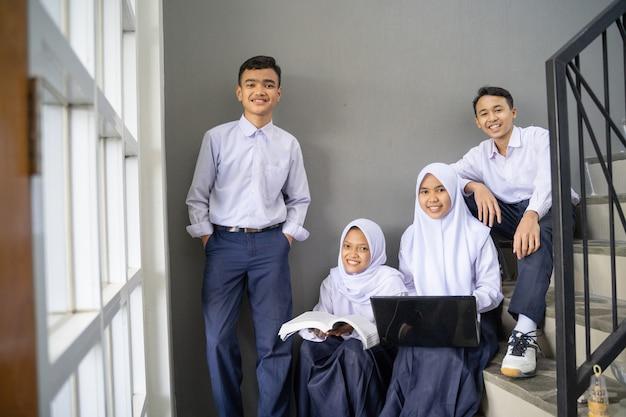 中学生の制服を着た4人のティーンエイジャーがノートパソコンと本を持ってカメラに向かって微笑む