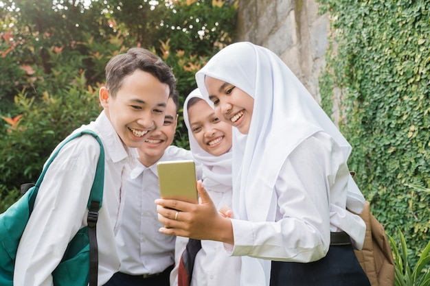 携帯電話を使って見ている中学生の制服を着た4人のティーンエイジャー