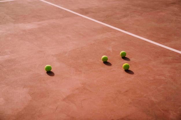 Четыре теннисных мяча на корте