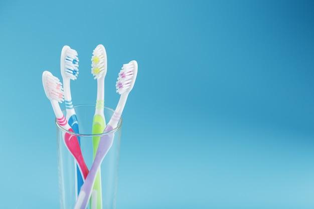 Четыре зубные щетки в стакане на синей поверхности