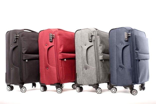 Четыре дорожных чемодана, изолированные на белом фоне