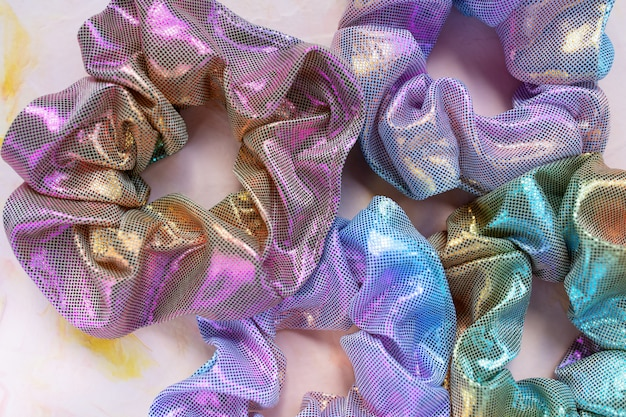 Четыре модные голографические радужные блестящие металлические резинки на розовом столе