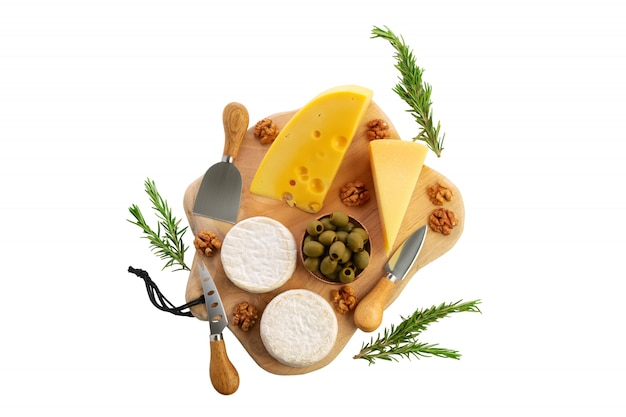 Four types of cheeses - parmesan, gouda, brie and camembert with olives on wooden board with cheese knives