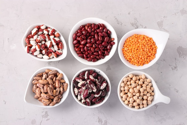 Four varieties of beans, red lentils and chickpeas - protein rich beans are located on a gray concrete background, top view, closeup