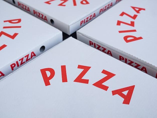 Четыре белые коробки для пиццы с красными буквами. сосредоточьтесь на буквах. концепция на вынос