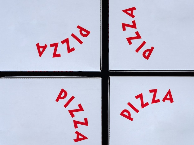 Четыре белые коробки для пиццы с красными буквами. концепция на вынос