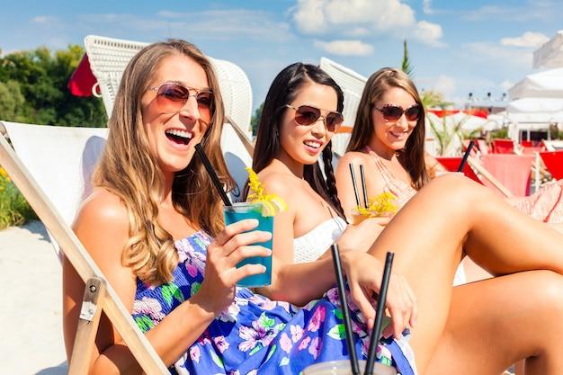 ビーチのラウンジャーに横たわって、日焼けした4人の女性