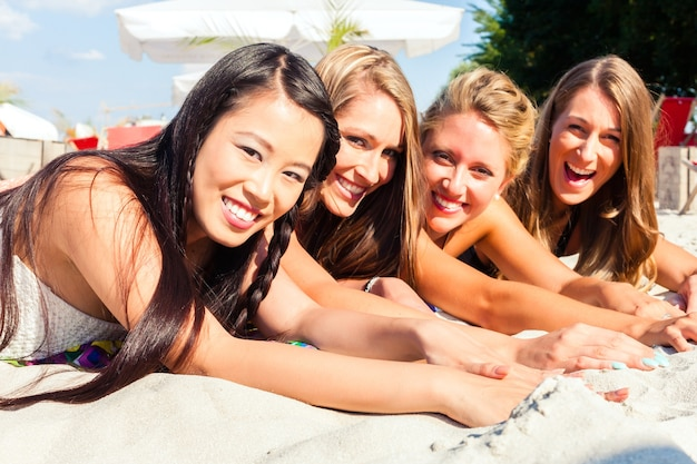 ビーチの砂の上に横たわって、太陽の下で日焼けしている4人の女性