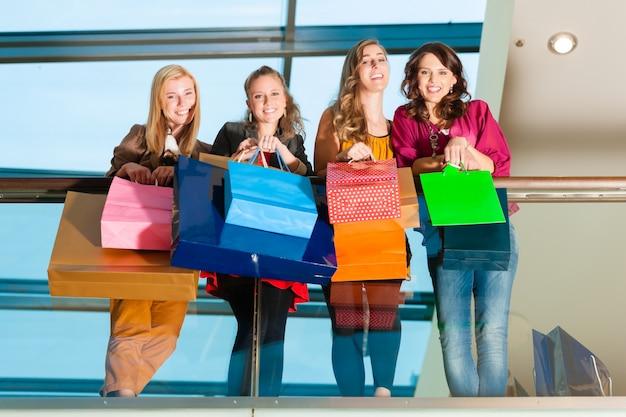 Four women friends shopping in a mall