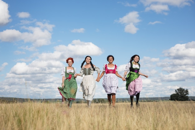 バイエルンの民族衣装を着た4人の女性が野原で走って笑う