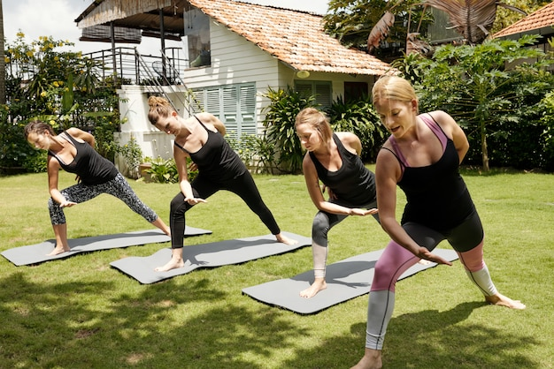 Four women practicing yoga outdoors on a sunny summer day