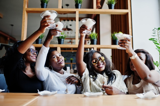Four women sitting on table at cafe and cheers with ice cream dessert
