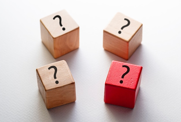 Four wooden blocks decorated with question marks