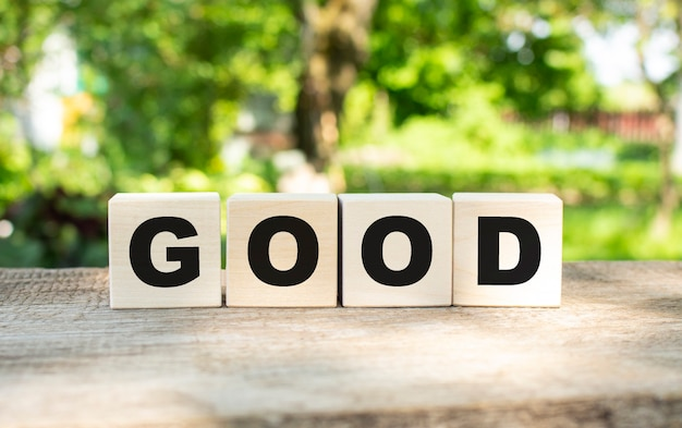Four wooden blocks lie on a wooden table against the backdrop of a summer garden and create the word good.