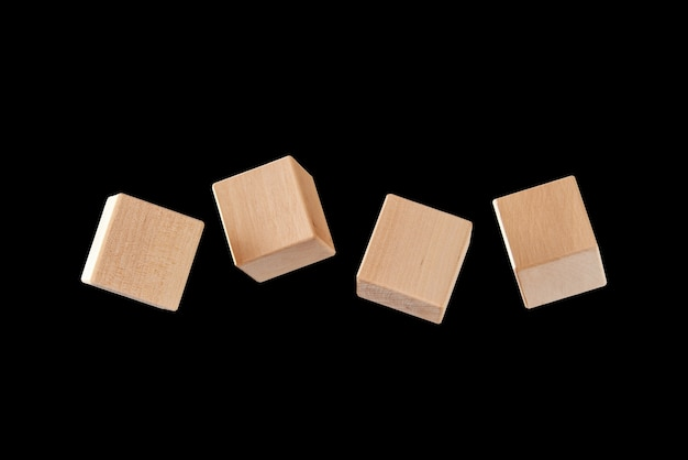 Four wooden cubes floating on a black background