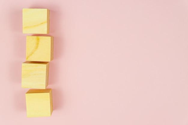 Четыре деревянных кубика на розовом фоне. творческая плоская планировка с копией пространства.