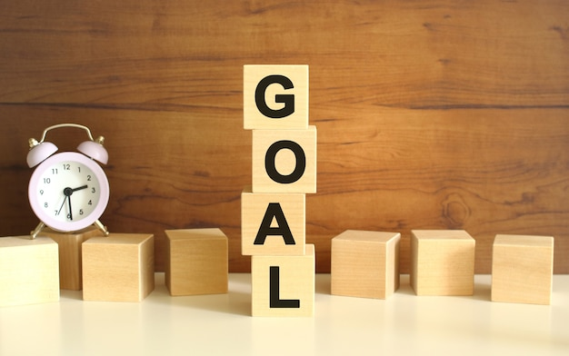 갈색 배경에 수직으로 쌓인 4개의 나무 큐브가 goal이라는 단어를 형성합니다.