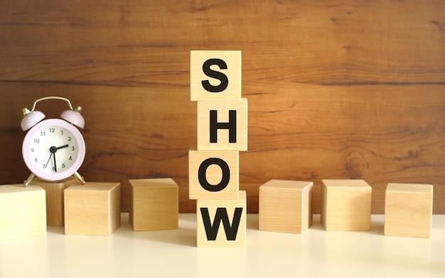 茶色の背景に垂直に積み重ねられた4つの木製の立方体は、showという言葉を形成します。