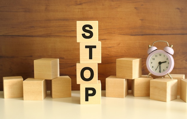 갈색 배경에 수직으로 쌓인 4개의 나무 큐브는 stop이라는 단어를 형성합니다.