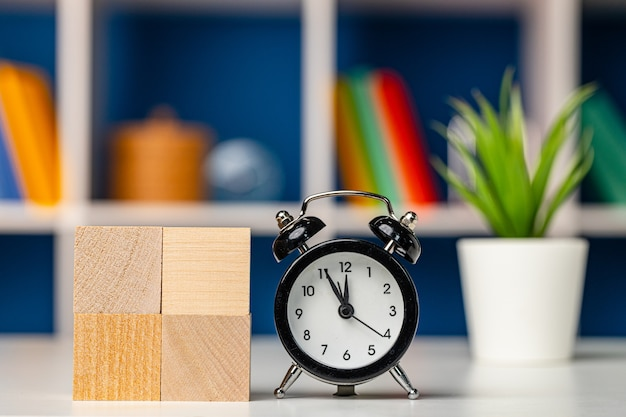 Four wooden cubes with copy space and alarm clock on desk