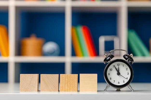 Четыре деревянных кубика с копией пространства и будильником на столе