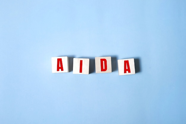 Four wooden cubes with letters aida meaning attention awareness interest desire action. business marketing concept.