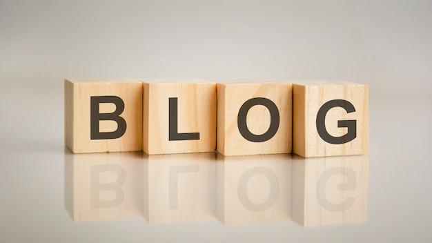 文字ブログと4つの木製の立方体。ビジネスマーケティングの概念。テーブルのミラーリングされた灰色の表面でのキャプションの反映