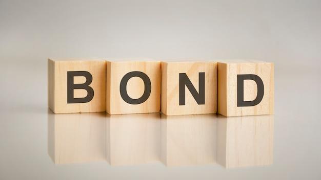 ボンドの文字が付いた4つの木製の立方体。ビジネスマーケティングの概念。テーブルのミラーリングされた灰色の表面でのキャプションの反映