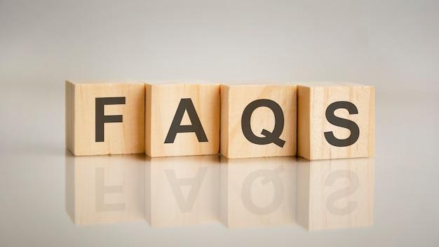 よくある質問の文字が付いた4つの木製の立方体。ビジネスマーケティングの概念。テーブルのミラーリングされた灰色の表面でのキャプションの反映