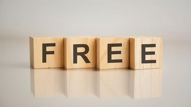 Четыре деревянных кубика с буквами free. бизнес-концепция маркетинга. отражение надписи на зеркальной серой поверхности стола