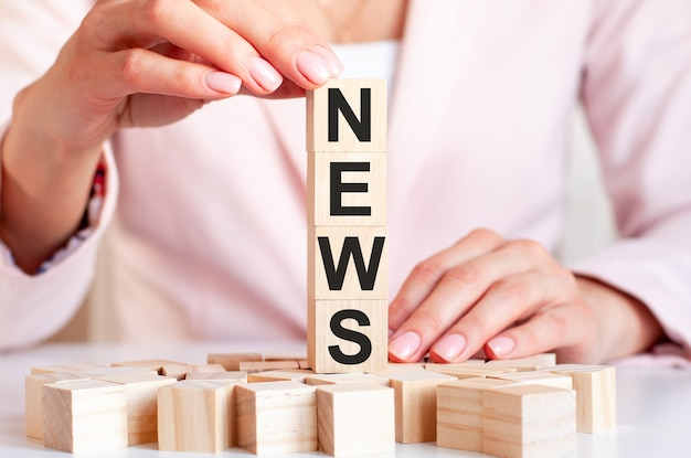 Four wooden cubes with word news, against the surface of female hands in pink clothes