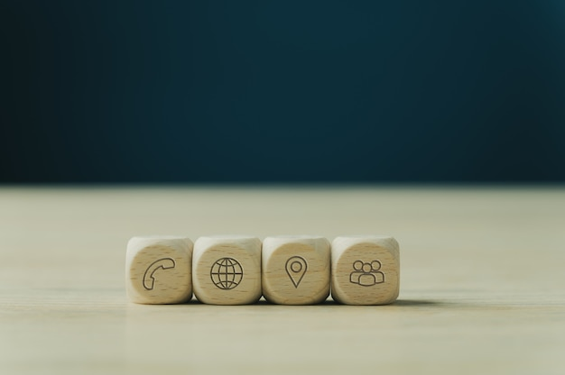 Four wooden dices with contact and information icons on them placed in a row. over blue background with copy space.