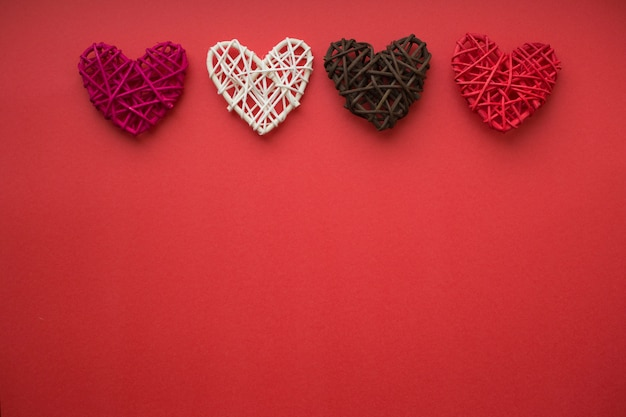Four wooden hearts lie horizontally on a red background. love concept. valentine day card. place for text