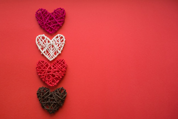 Four wooden hearts lie upright on a red background. love concept. valentine day card. place for text