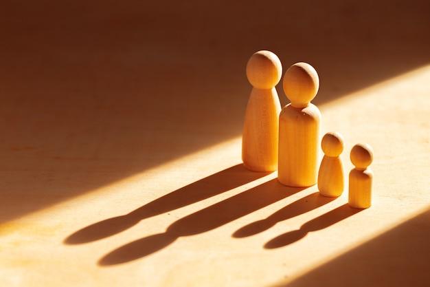나무 테이블에 햇빛에 4 개의 나무 인형 가족