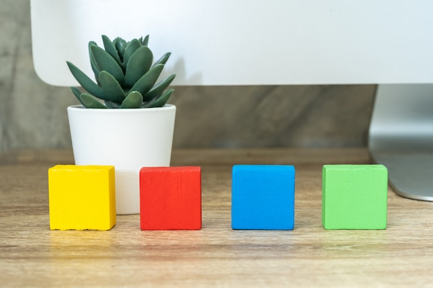 Four wooden toy cubes blocks on wooden table background with copy space