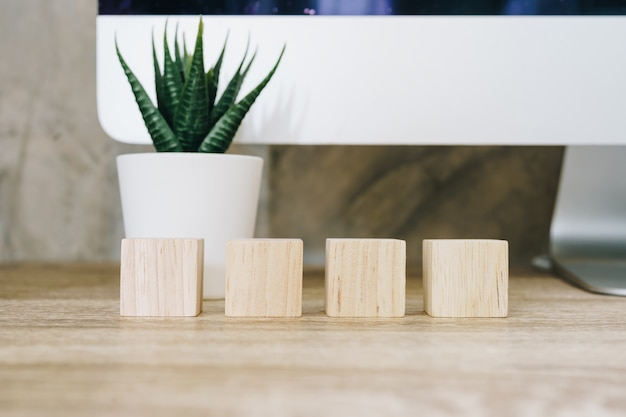Four wooden toy cubes on wooden table background with copy space