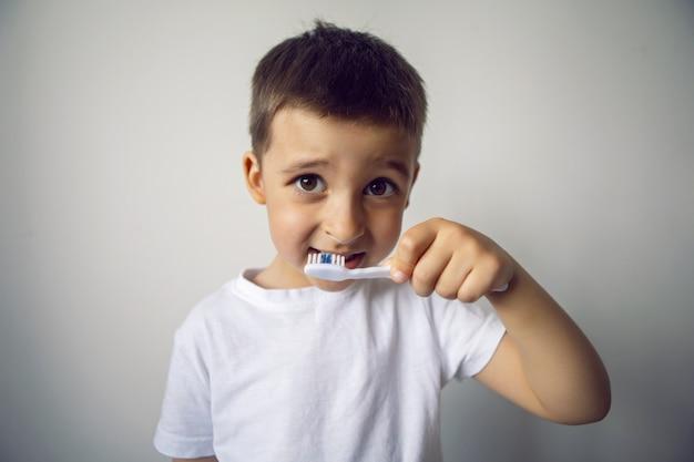 Четырехлетний мальчик стоит с зубной щеткой